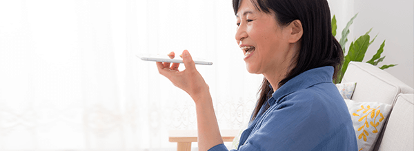 Mature Asian Woman using voice search function on her mobile phone